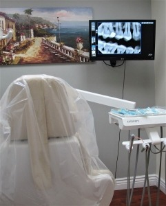 an examination room with a dental chair and monitor