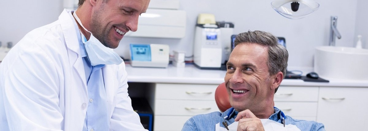male dentist smiling and showing results to a smiling male patient