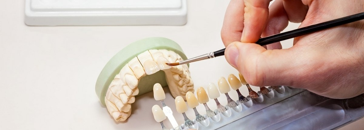 male dentist customizing a dental prosthetic
